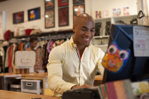 Man working at computer in consignment shop