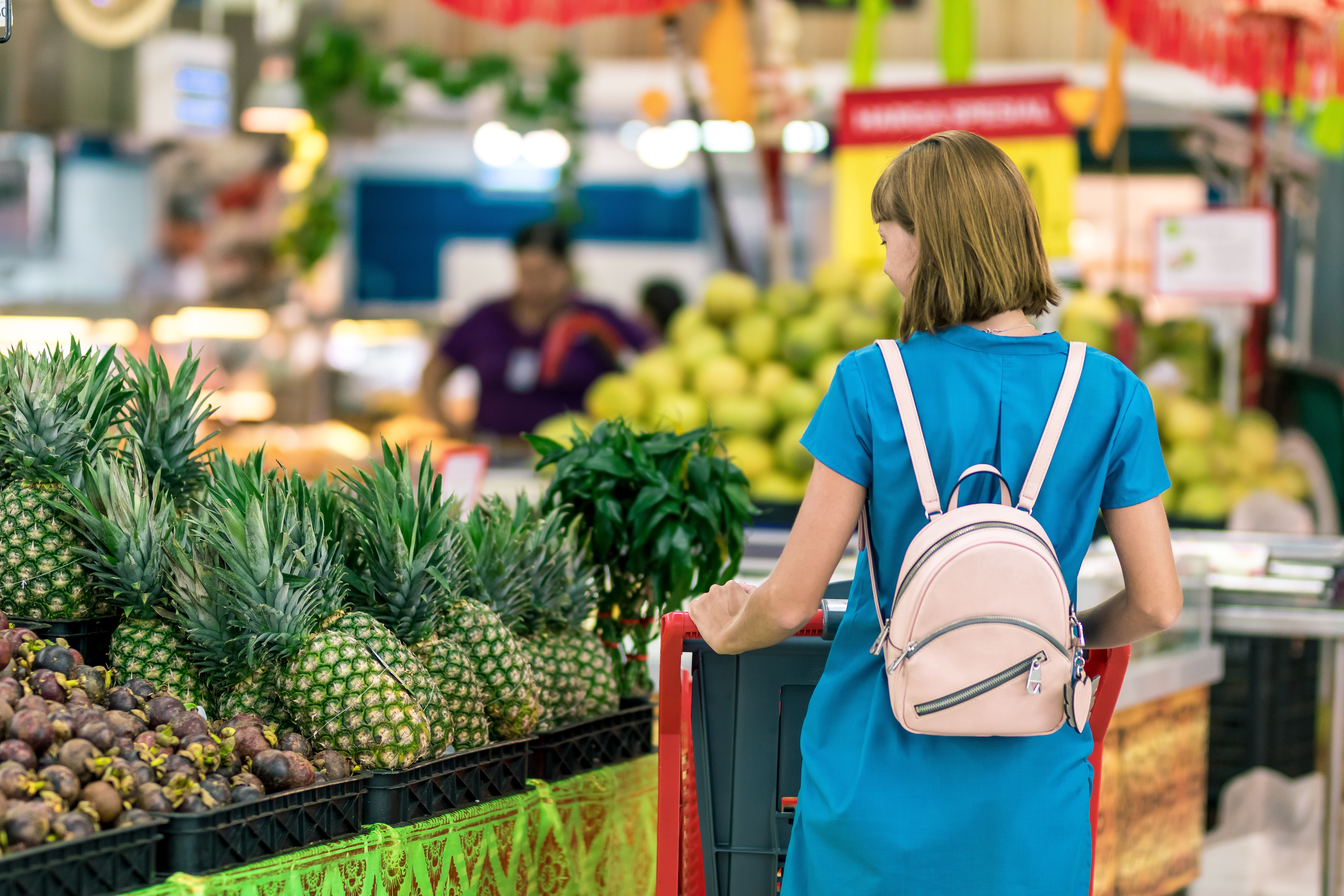 Woman with backpack shopping for pineapple
