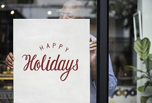 Small business owner hanging holiday sign in window