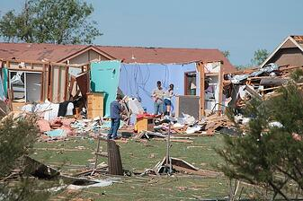 People cleaning up after tornado in Moore, OK